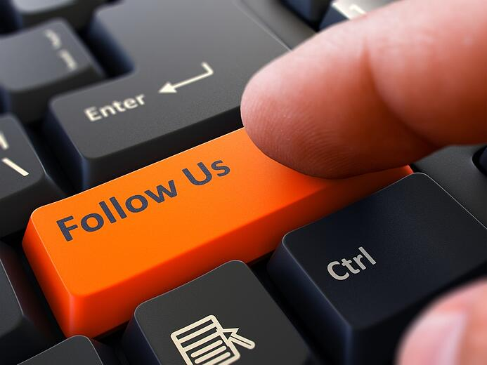 Follow Us Button. Male Finger Clicks on Orange Button on Black Keyboard. Closeup View. Blurred Background..jpeg
