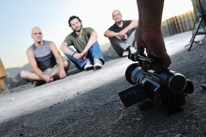 three young man siting on ground while modern video camera recording.jpeg