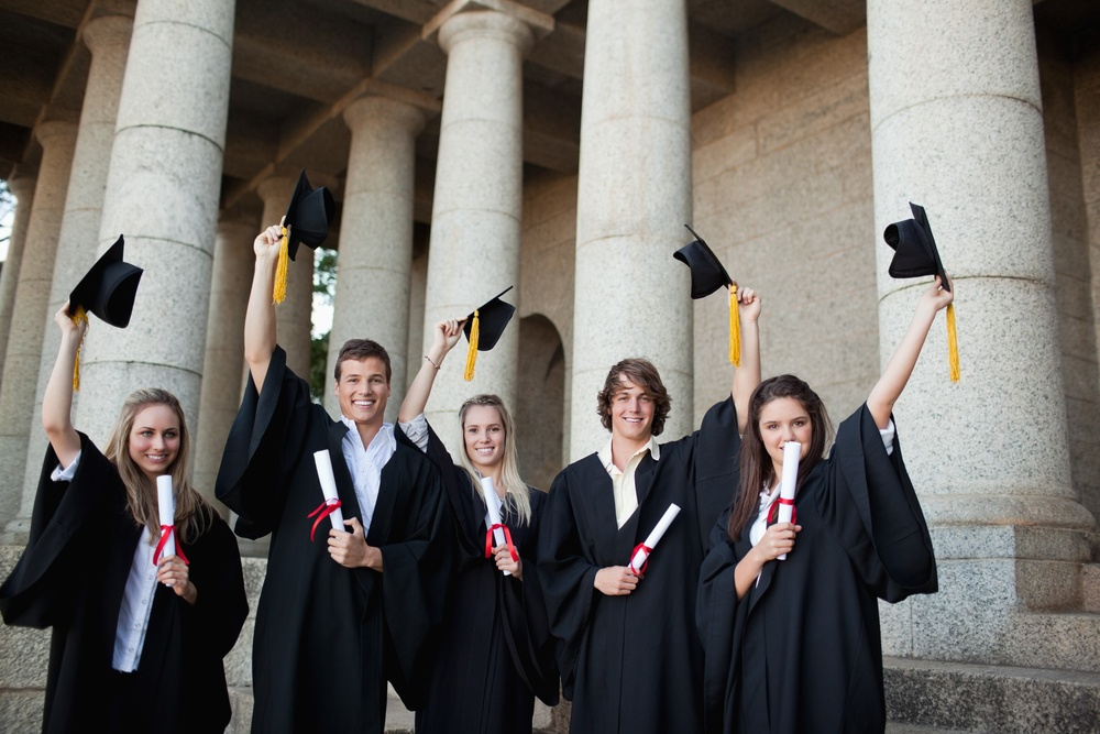 Graduates holding up their hats in front of the university.jpeg